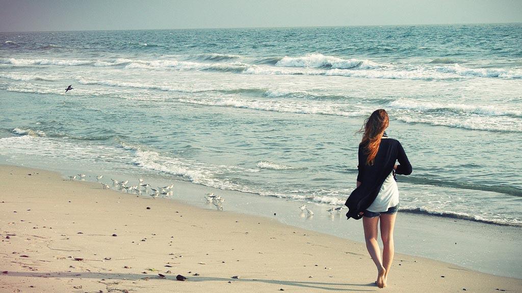 Красивая девушка гуляет по пляжу, телесно-ориентированная психотерапия